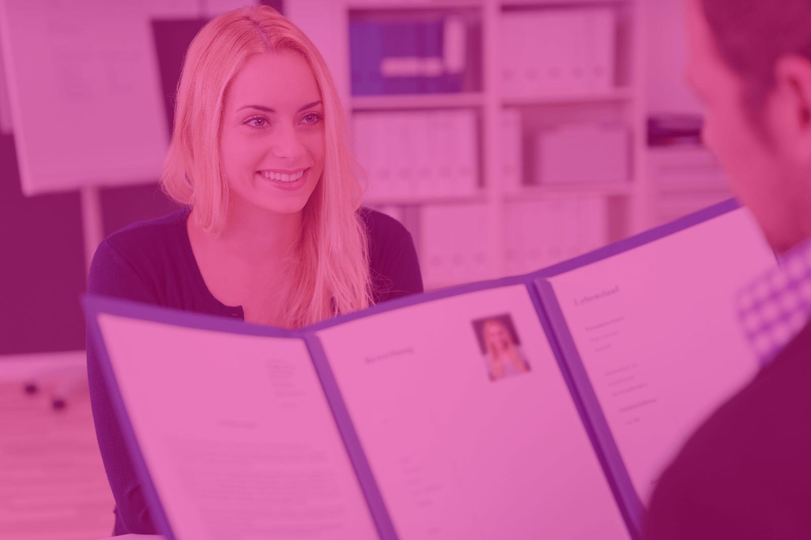 Eine junge Frau sitzt lächelnd jemandem in einem Bewerbungsgespräch gegenüber. Ihr gegenüber hält die Bewerbungsmappe aufgeschlagen vor sich.
