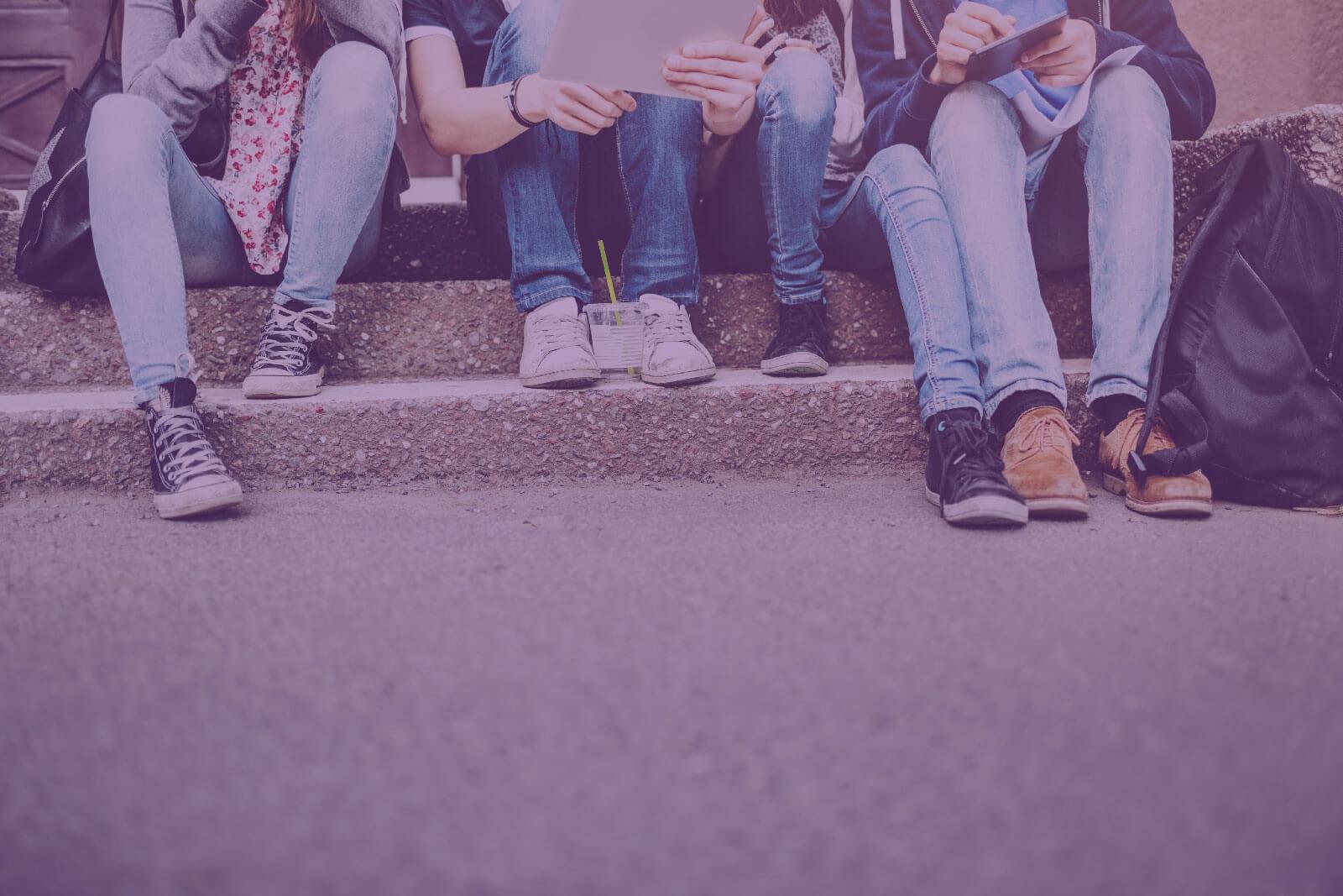 Jugendliche sitzen auf einer Treppe mit ihren Tablets