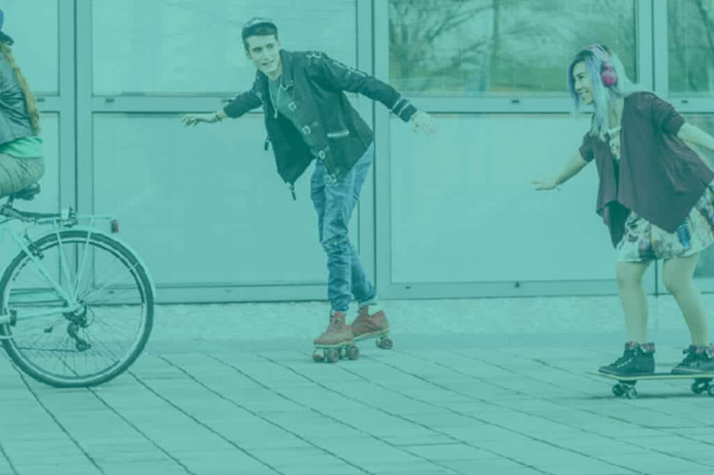 Vier Jugendliche; auf dem Rad, dem Skateboard und Rollschuhen